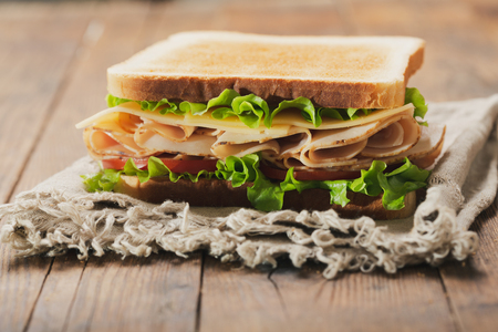 sandwich with ham and vegetables on wooden table