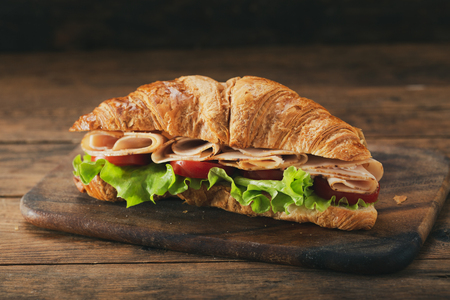 croissant sandwich with ham and vegetables on wooden table