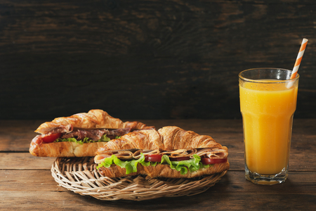 croissant sandwiches with ham and glass of orange juice on wooden table Stockfoto