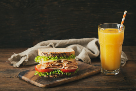 sandwich with ham and glass of orange juice on wooden table