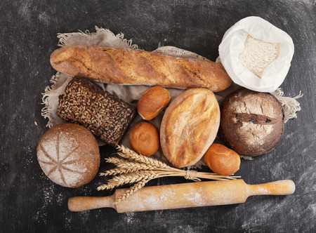 fresh bread with wheat ears, flour and kitchen utensils on dark board, top view Stockfoto