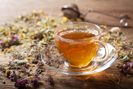 Cup of herbal tea with various herbs on wooden table