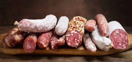 Différents types de salami et de saucisses sur une planche de bois