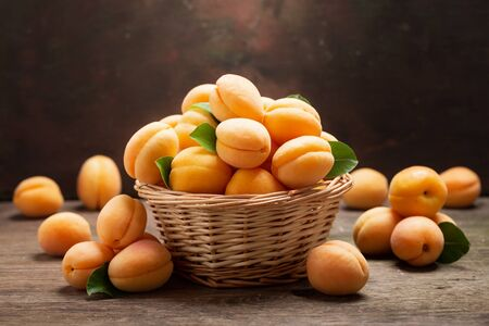 Fresh ripe apricots with leaves in a basket on wooden table
