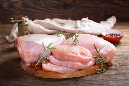 fresh turkey meat with rosemary on wooden board Stockfoto