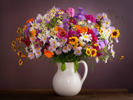 bouquet of summer flowers in a jar on wooden table Stockfoto