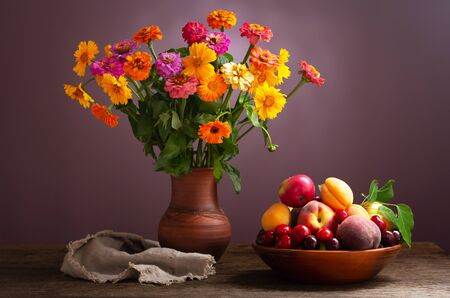 still life with bouquet of summer flowers in a jar and fresh fruits on wooden table Reklamní fotografie - 127926260