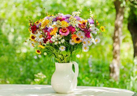 bouquet of summer flowers in a jar in a gardenin a garden Reklamní fotografie