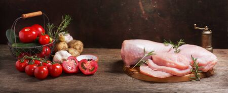 fresh turkey meat with ingredients for cooking on wooden board,