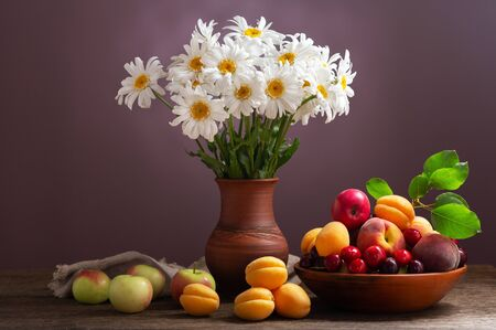 still life with bouquet of daisy flowers in a jar and fresh fruits on wooden table Reklamní fotografie - 127926808