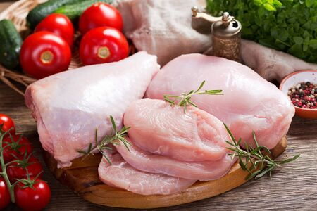 fresh turkey meat with ingredients for cooking on wooden table