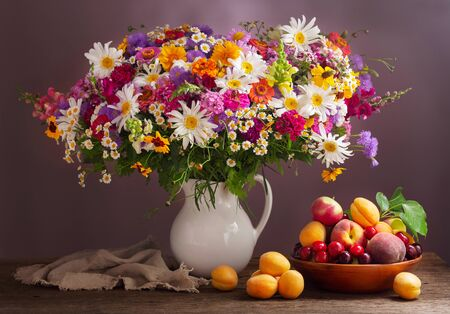 bouquet of summer flowers in a jar and fresh fruits on wooden table