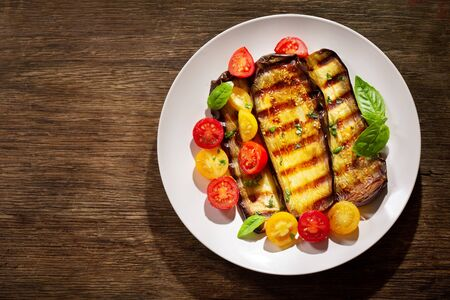 plate of grilled eggplants with colorful tomatoes and green basil on wooden background, top view Reklamní fotografie - 127584236