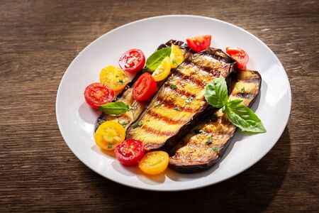 plate of grilled eggplants with colorful tomatoes and green basil on wooden table Reklamní fotografie