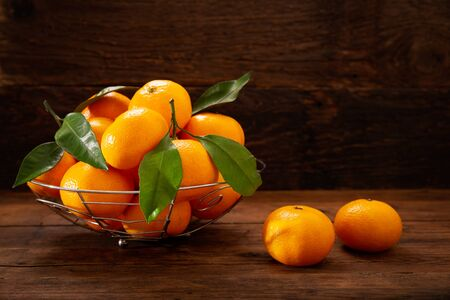 Fresh mandarin oranges fruit or tangerines with leaves on wooden table Stockfoto