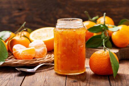 glass jar of orange tangerine or mandarin jam with fresh fruits on wooden table Reklamní fotografie