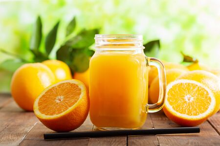 glass jar of fresh orange juice with fresh fruits on wooden table Reklamní fotografie - 127584509