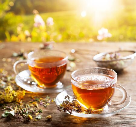Cups of herbal tea with various herbs on wooden table at sunset Reklamní fotografie - 128655696