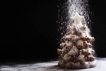 Christmas food. Christmas Tree made from Gingerbread cookies and snow from icing sugar on dark background