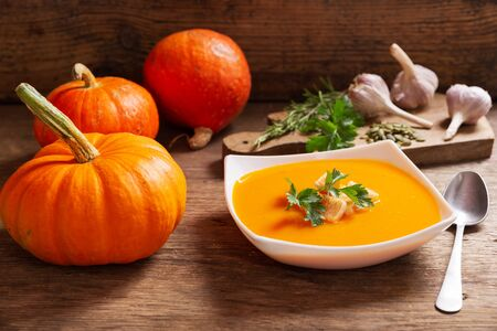 bowl of pumpkin soup with ingredients for cooking on wooden table Reklamní fotografie - 128655769