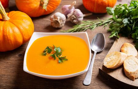 bowl of pumpkin soup with ingredients for cooking on wooden table Stockfoto