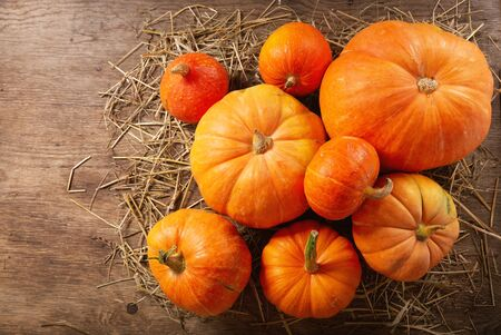 Orange pumpkins on wooden table. Autumn harvest background, top view Stockfoto