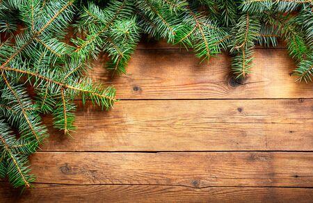 Sfondo di Natale. Decorazione natalizia con rami di abete su fondo in legno, vista dall'alto