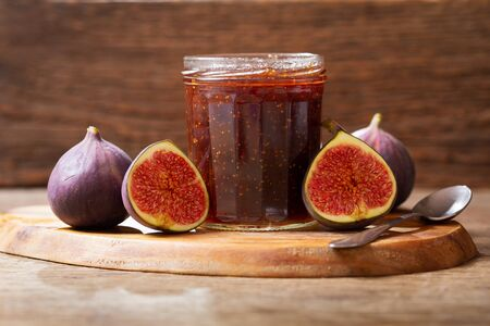 glass jar of figs jam with fresh fruits on wooden table