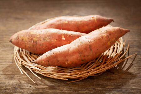 close up of fresh sweet potato on a wooden table