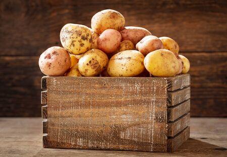 fresh raw potatoes in a wooden box