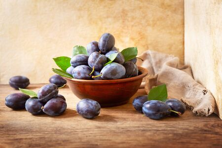 bowl of fresh plums with leaves on wooden table Stock Photo