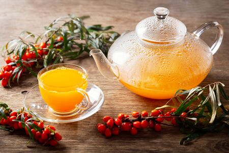 teapot and cup of hot sea buckthorn tea with fresh berries on wooden table Reklamní fotografie