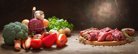 fresh chopped meat with rosemary and fresh vegetables for cooking on a wooden table