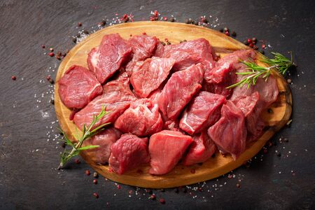 fresh chopped meat with rosemary on wooden board, top view Reklamní fotografie