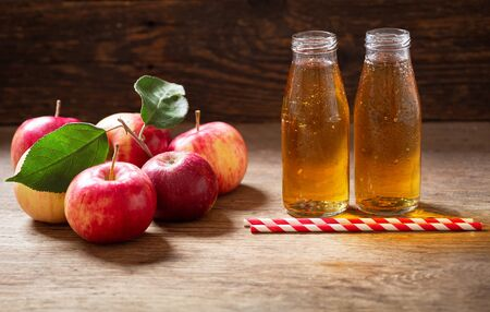bottles of fresh apple juice with fresh fruits on wooden table Reklamní fotografie