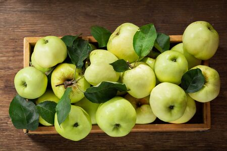 fresh apples with leaves in a box on a wooden table, top view