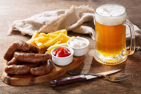 fried sausages with french fries on wooden board and cold mug of beer Reklamní fotografie