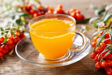 cup of hot sea buckthorn tea with fresh berries on wooden table