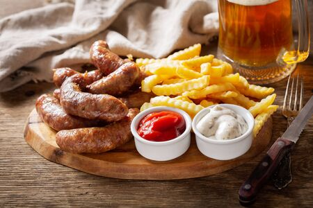 fried sausages with french fries and mug of beer on a wooden table