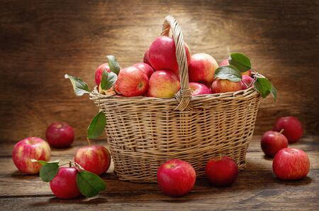 fresh apples with leaves in a basket on a wooden table Reklamní fotografie