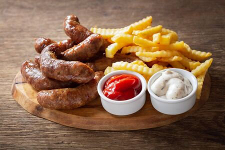 fried sausages with french fries on a wooden board