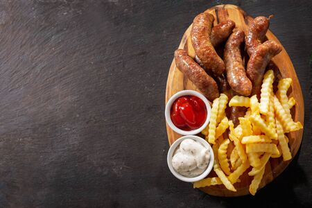 fried sausages with french fries on a wooden board, top view