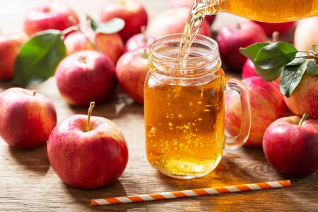 fresh apple juice pouring from bottle into glass jar