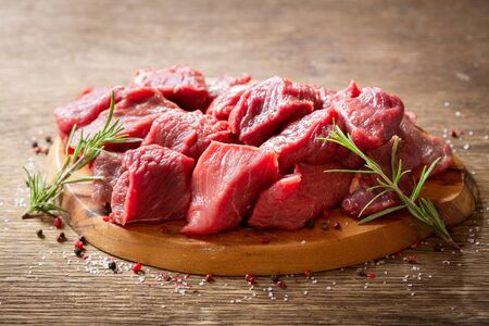 fresh chopped meat with rosemary on wooden board