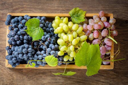 mix of fresh ripe grapes with leaves in a wooden box, top view