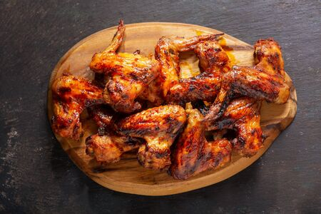 grilled chicken wings on a wooden board, top view