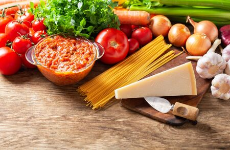 sauce bolognese with fresh vegetables for cooking, spaghetti and parmesan on wooden table