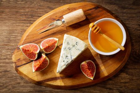 slice of blue cheese with fresh figs and honey on wooden board, top view