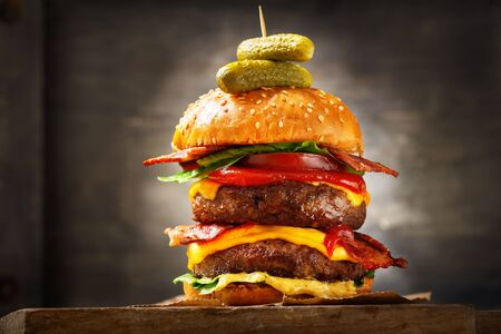 big double hamburger with cheese, bacon, salad and vegetables on wooden  board Reklamní fotografie