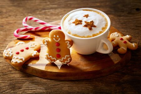 Christmas drink. Cup of cappuccino coffee with stars drawing and gingerbread cookie on wooden board Stockfoto